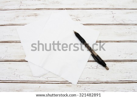 Blank Napkins with pen for your message, A napkins that are blank with a pen over a distressed wood background  - stock photo