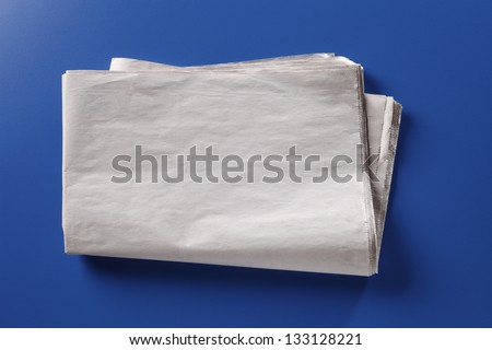 Blank nespaper on the blue background - stock photo