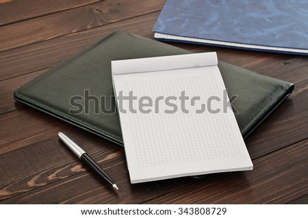 Blank note book and pen on leather folder on the office desk closeup. Top view - stock photo