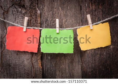 blank note hanging on old wooden background - stock photo
