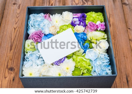 blank note on flowers in the box - stock photo