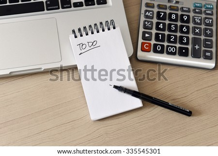 Blank Note Pad, Calculator, Computer, Pen on the Table - To do list