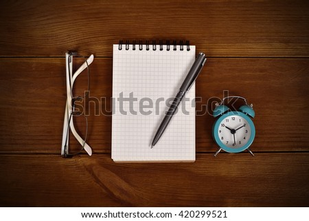 blank note pad, pen, clock and glasses on wooden table - stock photo