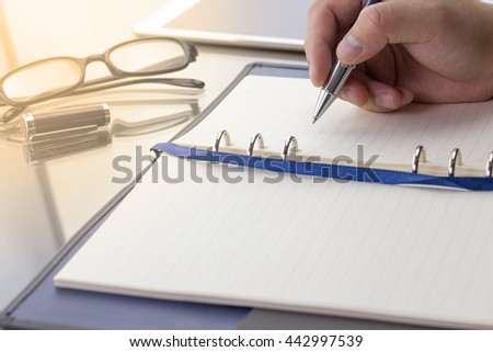Blank note paper with pen, digital table and glasses. Theme business meeting concept. Warm tone.