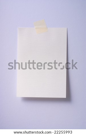 Blank note stuck to notice board with masking tape - stock photo