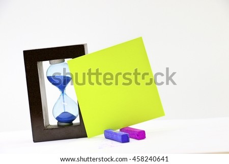Blank note with sand clock for writing message on white background - stock photo