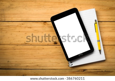 blank notebook and a yellow pen with mobile phone on  wooden table in warm tone.