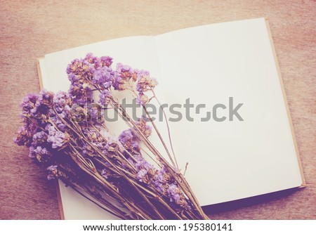 Blank notebook and dried statice flowers, nostalgic still life, retro instagram filter effect - stock photo