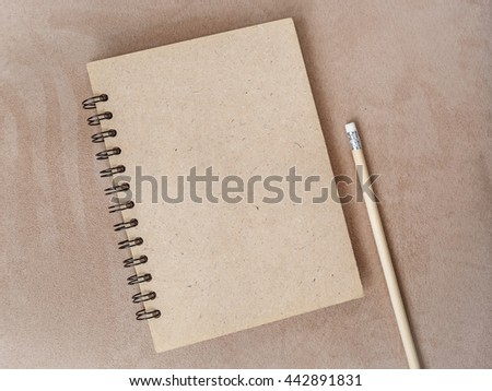 Blank notebook and pencil on natural brown colour background - stock photo