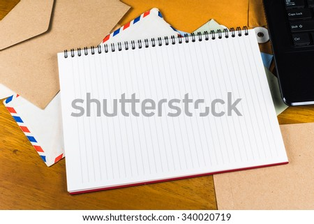 Blank notebook as copy space on envelopes with computer laptop