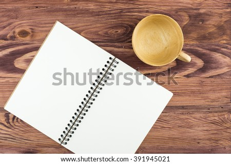 Blank notebook on a wooden table background.