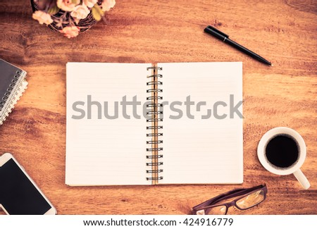 blank notebook on wood table top view add vintage color