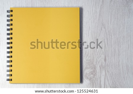 Blank notebook on wooden desk - stock photo