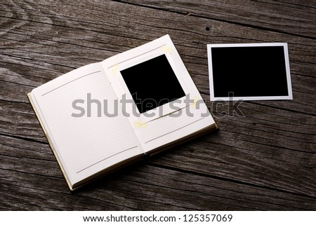 Blank notebook paper and instant photos on wooden background - stock photo