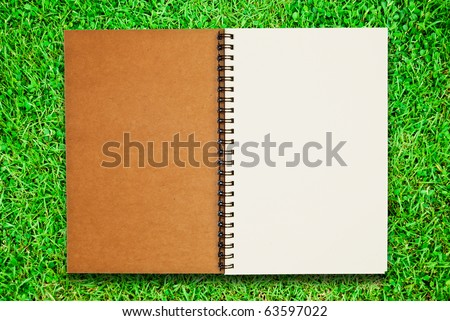 blank notebook recycle paper open two page with copy space area for multipurpose use open on green grass field