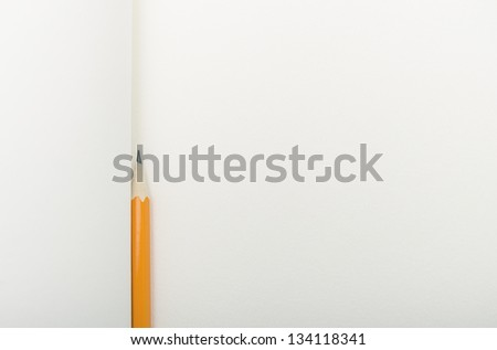 Blank notebook with a pencil resting on it.