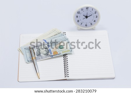 Blank notebook with dollar bill and clock for money and time concept - stock photo