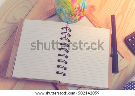 blank notebook with pen and calculator on wooden table, business concept with retro effect.