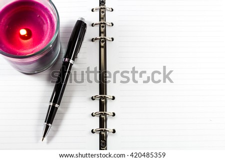 Blank notebook with pen and candle in cup copy space for text on right - stock photo