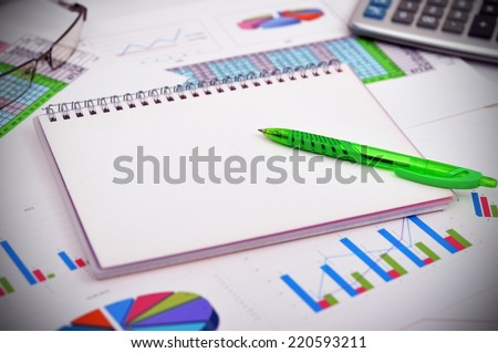 blank notebook with pen and financial charts