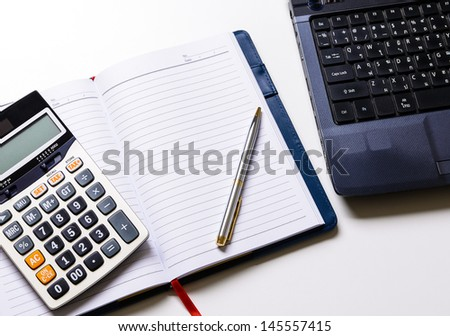 Blank notebook with pen and laptop and calculator on the desk - stock photo