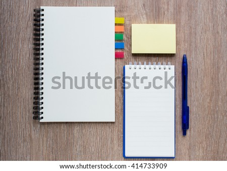blank notebook with pen and post it on wooden background - stock photo