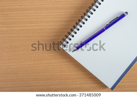 blank notebook with pen on wooden table background