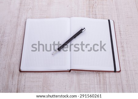 blank notebook with pen on wooden table, business concept. - stock photo