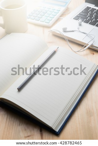 blank notebook with pencil and laptop on wood background