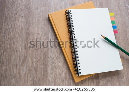 blank notebook with pencil on wooden background - stock photo