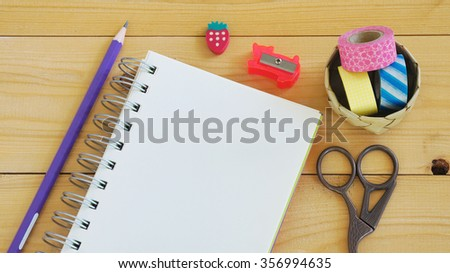 Blank notebook with pencil, rubber, sharpener, washi tapes, scissors on wooden table