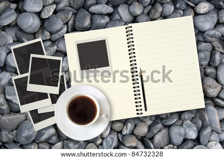 blank notebook with photo frame and coffee cup on stone background