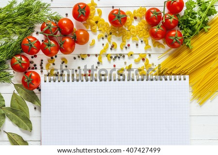 Blank notebook with spaghetti, tomatoes, parsley, dill and spice are lying on the wooden table. Space for text. Recipe book or cookbook. Copy space, top view. - stock photo