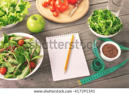 Blank notebook with various salad leaves and apple, glass of water, flax seed and measuring tape. Healthy eating, weight loss and diet concept, top view - stock photo