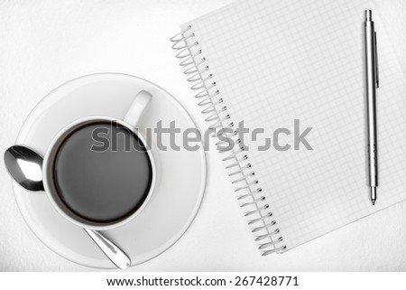 Blank notepad, a pen and a cup of coffee on a white table - stock photo