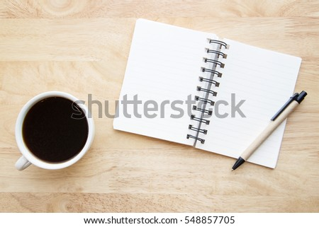 Blank notepad and black coffee on wood table.