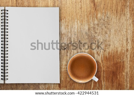 Blank notepad and coffee cup on wooden table.