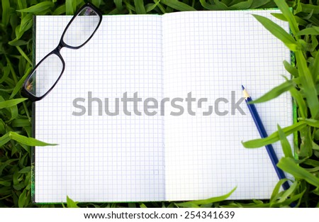 Blank notepad for copy space on green grass.  - stock photo