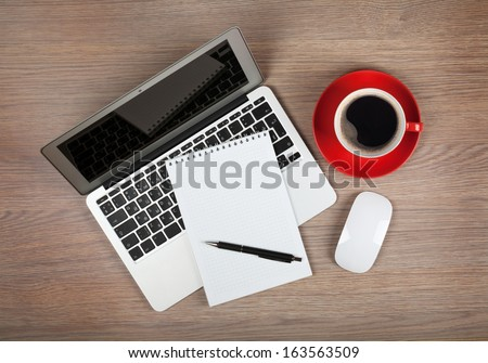 Blank notepad over laptop and coffee cup on office wooden table - stock photo