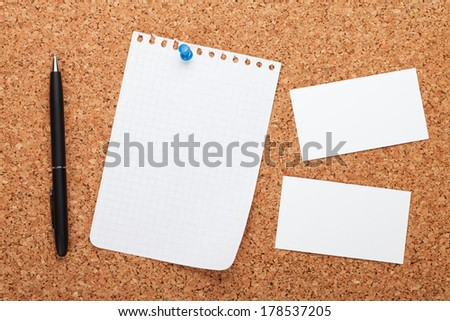 Blank notepad paper, business cards and pen on cork wood notice board - stock photo