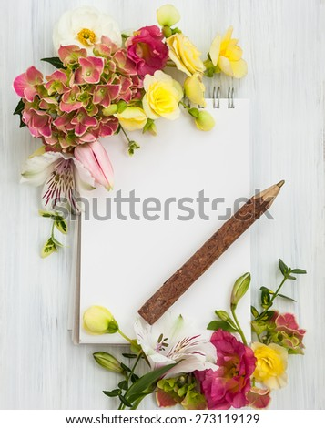 Blank notepad,pen and flowers over white wooden background. Top view with copy space