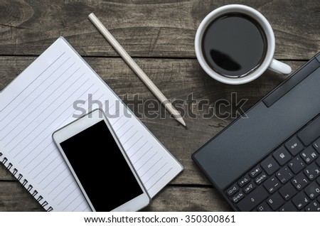 Blank notepad, phone, laptop and coffee cup on office wooden table - stock photo