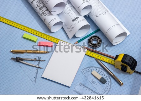 blank notepad, rolls of engineering drawings with tools on graph background