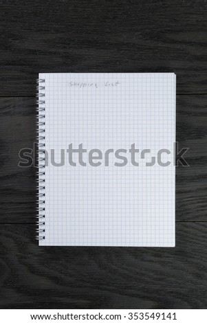 blank notepad with chequered pages on gray wood table with shopping list phrase, top view - stock photo