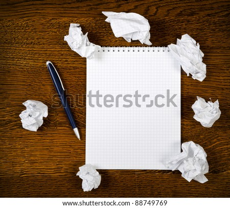 Blank notepad with ink pen on wooden desk - stock photo