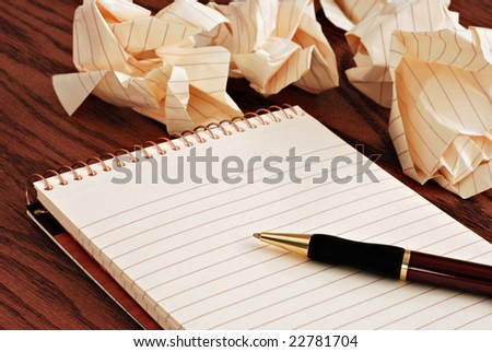 Blank notepad with ink pen on wooden desk.  Crumpled paper in soft focus in background - conceptual image for creative block. - stock photo