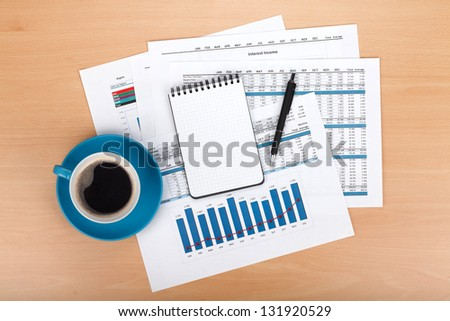 Blank notepad with pen and coffee cup over financial documents - stock photo