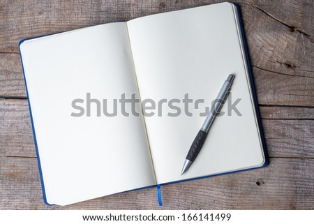Blank notepad with pen on office wooden table  - stock photo
