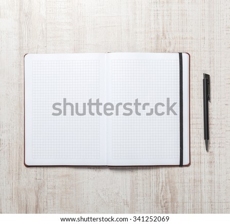 Blank notepad with pen on office wooden table. - stock photo