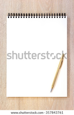 Blank notepad with pen on wood background